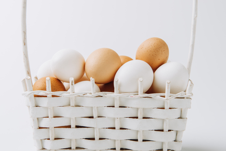 white and brown eggs laying in wicker basket on white background Stock Photo