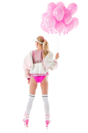 Attractive young woman in pink roller blades holding balloons isolated on white