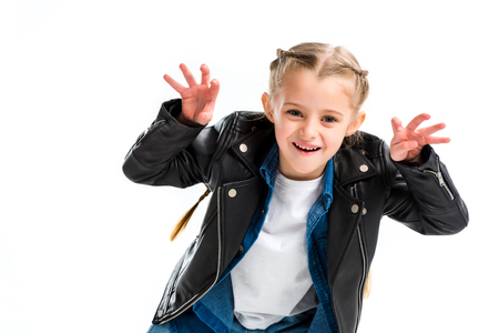 Stylish child with pigtails wearing leather jacket doing scaring gesture isolated on white Stock fotó