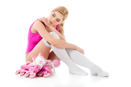 Young girl wearing pink swimsuit sitting with roller skates isolated on white