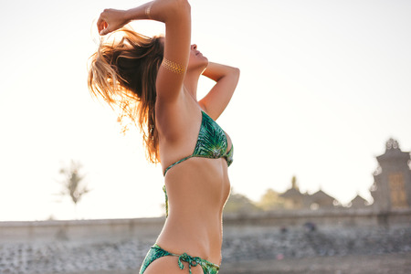 side view of beautiful young woman in bikini playing with hair with sunlight on background Stock Photo