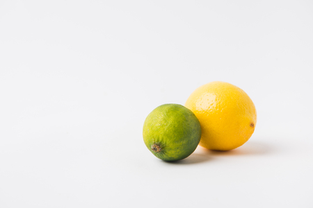 green lime and lemon laying on white background Фото со стока