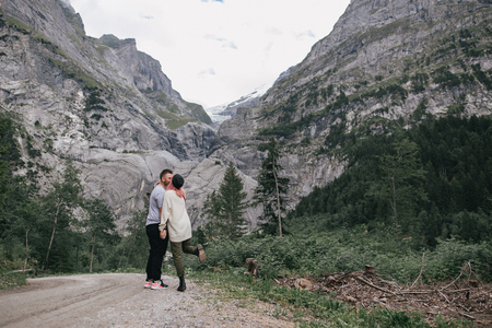 happy young couple in love kissing while walking in majestic mountains Фото со стока