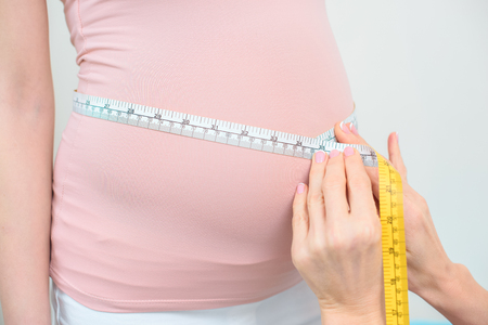 cropped shot of obstetrician gynecologist measuring belly size of pregnant woman with measuring tape