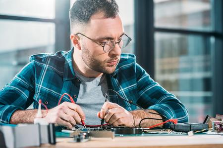 Repairman testing circuit board and checking multimeter measurements