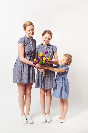 smiling mother and daughters in similar dresses with bouquet of tulips isolated on grey