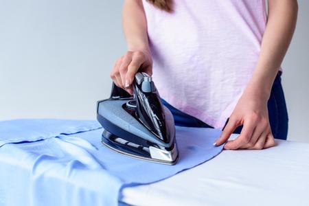 cropped shot of woman ironing shirt at home