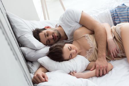 Pareja joven en pijama durmiendo juntos en la cama