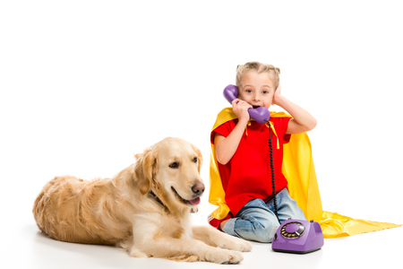 Lying golden retriever  with shocked little supergirl talking on phone isolated on white Stock Photo