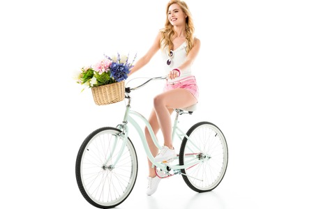 Young smiling girl riding bicycle with flowers in basket isolated on white Imagens