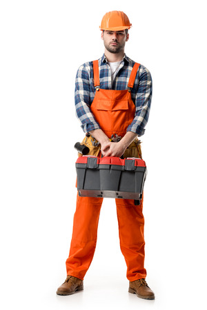Confident handyman in orange overall and hard hat holding tool box isolated on white