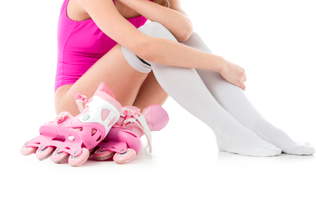 Cropped view of girl wearing pink swimsuit sitting with roller skates isolated on white