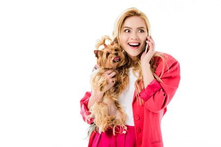 Young girl wearing pink jacket holding Yorkshire terrier and talking on phone isolated on white Stock Photo