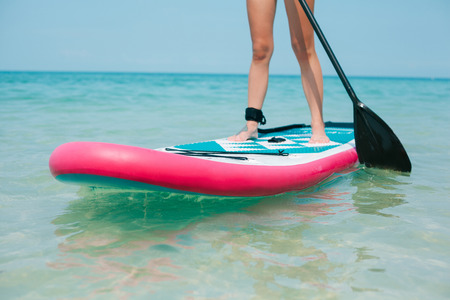 cropped view of woman on stand up paddle board on sea 免版税图像