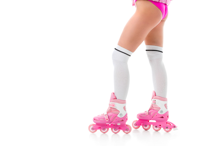 Cropped view of woman in pink roller skates isolated on white