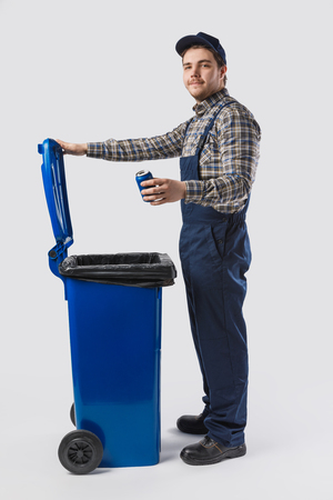 side view of young cleaner in uniform with can standing at trash bin isolated on grey Stock Photo