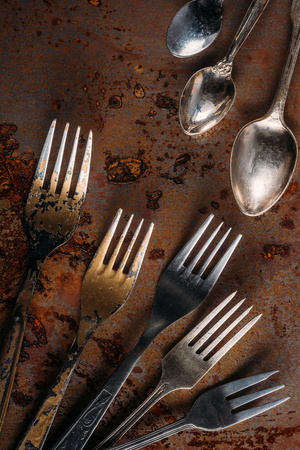 Vintage cutlery set on rusted background