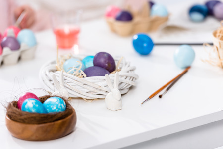 Easter eggs and paint on white table Stock Photo