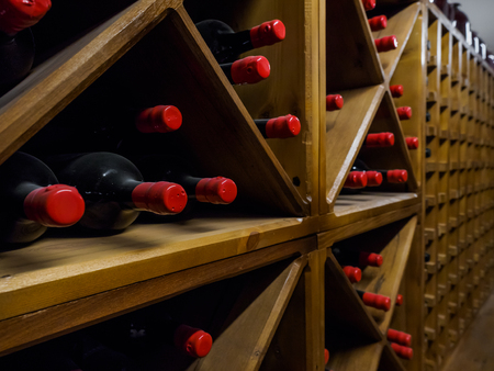 close up view of arranged wine bottles in cellar