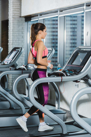 sporty woman training on treadmill at gym