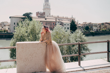 beautiful elegant girl in glamorous dress posing at river in Verona, Italy Banque d'images