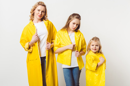 stylish beautiful mother and daughters in yellow raincoats on white