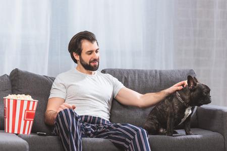 handsome loner palming bulldog on sofa at home