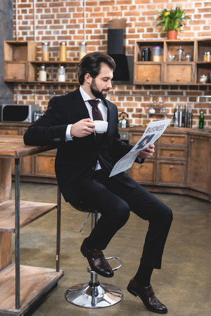 handsome loner businessman reading newspaper and holding cup of coffee at kitchen
