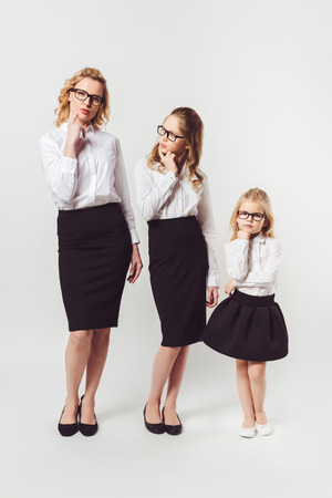stylish mother and daughters in similar businesswomen costumes on white