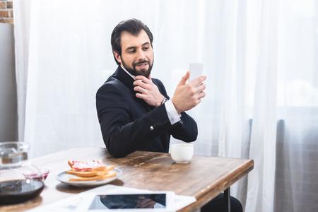 smiling loner businessman taking selfie with smartphone at kitchen
