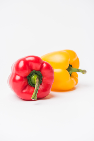 red and yellow bell peppers laying on white background