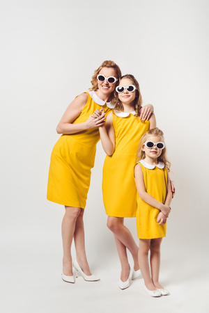 mother and daughters in similar retro style yellow dresses and sunglasses on white