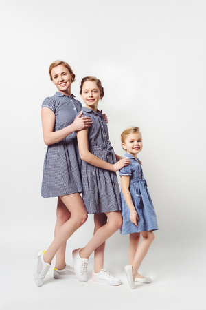 mother and daughters in similar dresses standing in row on white 스톡 콘텐츠