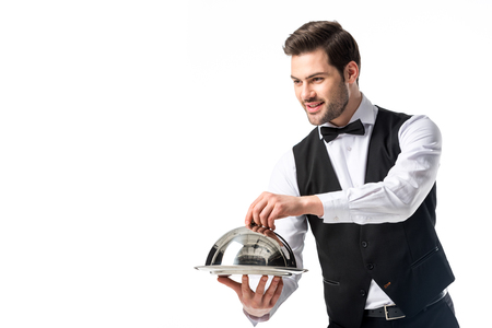 portrait of handsome bearded waiter in suit vest with serving tray isolated on white Stockfoto