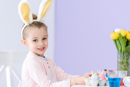 Child girl playing wearing bunny ears by table with Easter colored eggs Stock Photo - 111370417