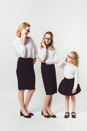 mother and daughters in similar businesswomen costumes on white