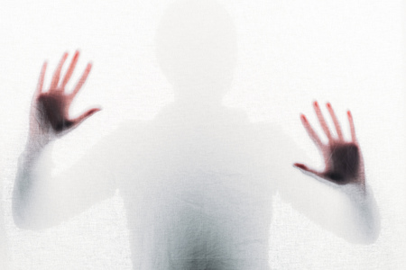 blurry silhouette of person touching frosted glass with hands Banque d'images - 111370543
