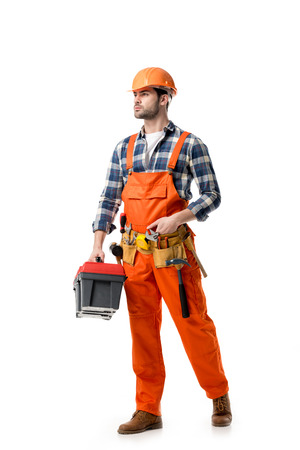 Young confident repairman in orange overall holding tool box isolated on white 写真素材 - 111370544