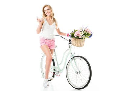Blonde woman standing by bicycle with flowers in basket isolated on white