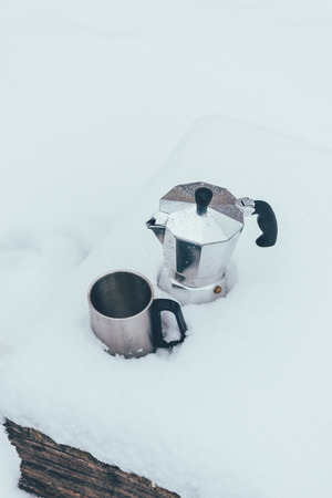 close up view of cup and coffee maker in snow Imagens