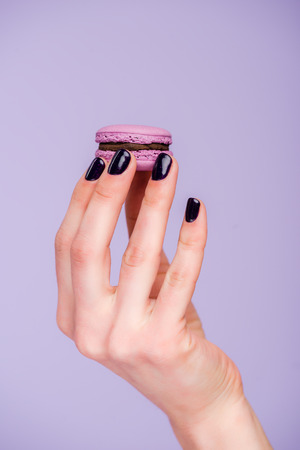 Female hand with macaron isolated on violet