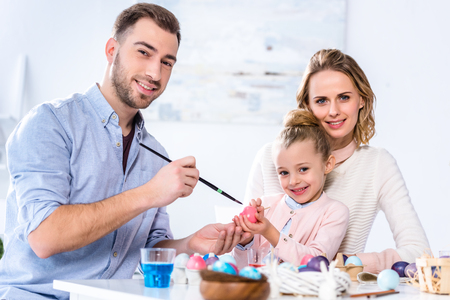 Father and daughter smiling while painting Easter eggs