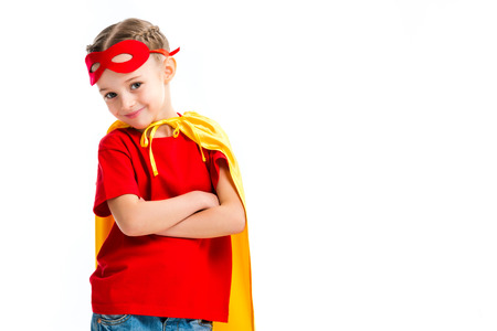 Smiling little supergirl wearing yellow cape with red mask for eyes on forehead isolated on white