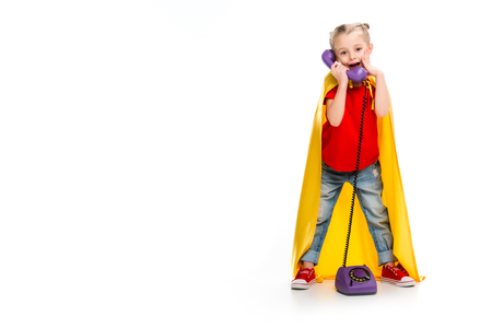 Shocked little supergirl wearing yellow cape and talking on phone isolated on white Stock Photo