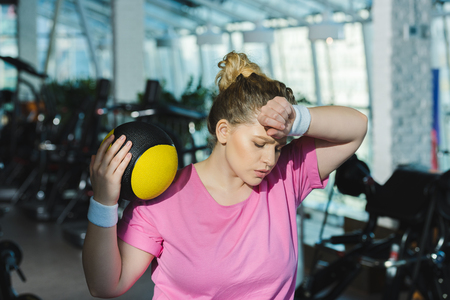 tired overweight woman with hand on forehead and medicine ball on shoulder