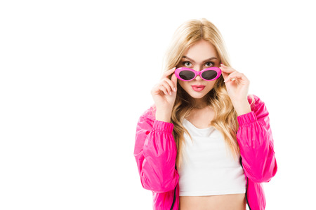Young girl wearing pink hoodie looking over sunglasses isolated on white