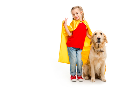 Smiling supergirl in yellow cape gesturing peace sign with golden retriever beside isolated on white Stock Photo