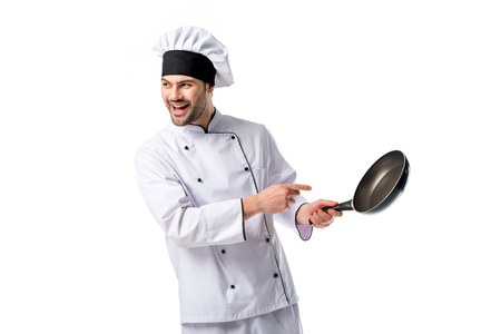 smiling chef in uniform pointing at frying pan in hand isolated on white Фото со стока