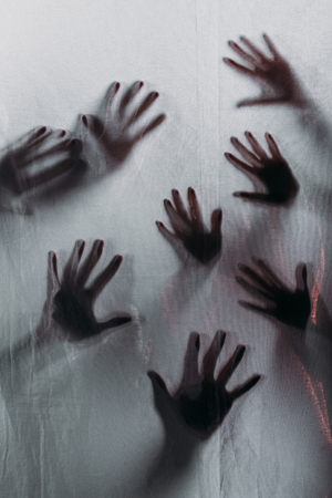 blurry scary silhouettes of human hands touching frosted glass Reklamní fotografie - 111565489
