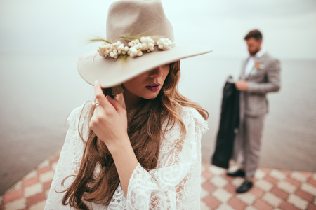 beautiful bride in wedding dress and hat in boho style on pier at lake, groom standing behind Stock Photo
